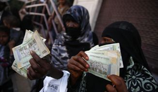 "FILE - In this Nov. 14, 2015 file photo, women display paper currency after receiving cash support from UNICEF, in Sanaa, Yemen. Yemen's Central Bank said Sunday, Aug. 13, 2017 that the Saudi-led coalition is ""strangling"" the economy by preventing planes from flying in newly-minted cash, reflecting a struggling between the government and the United Arab Emirates, key members of the military alliance. Both are at war with the Shiite Houthi rebels, who control much of northern Yemen, including the capital, Sanaa. (AP Photo/Hani Mohammed, File)"