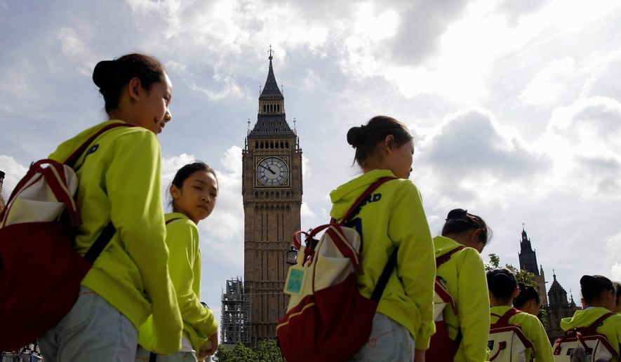 Tourists walk past the Palace of Westminster and the Queen Elizabeth Tower in London on Monday. Big Ben will fall silent next week as a major restoration project gets underway. The bongs of the iconic bell will be stopped on Aug. 21 to protect workers. (Associated Press)
