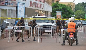Security forces stands guard outside the site of a restaurant attacked in Ouagadougou, Burkina Faso, Monday, Aug. 14, 2017. The death toll is still rising and authorities said many of the victims were children dining with their families on Sunday night. (AP Photo/ Ahmed Yempabou Ouoba)