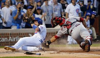 Chicago Cubs' Kris Bryant, left, scores past Cincinnati Reds catcher Devin Mesoraco off a double by Anthony Rizzo during the first inning of a baseball game Monday, Aug. 14, 2017, in Chicago. (AP Photo/Charles Rex Arbogast)