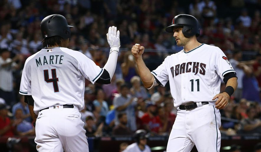 Arizona Diamondbacks' A.J. Pollock (11) and Ketel Marte (4) celebrate after both scored runs against the Houston Astros during the fourth inning of a baseball game Tuesday, Aug. 15, 2017, in Phoenix. (AP Photo/Ross D. Franklin)