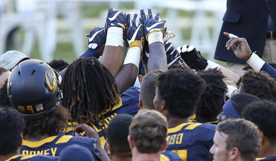 FILE - In this Aug. 27, 2016 file photo, California Golden Bears players reach up to touch the trophy presented to them ofter defeating the Hawaii Rainbow Warriors at the end the opening game of the U.S. college football season at Sydney's Olympic stadium in Sydney. Despite losing two of its top players to the NFL, Stanford will be heavily favored against Rice when U.S. college football returns Down Under for the second year in a row. The Aug. 27, 2017 game will be played at midday Sunday in Australia, Saturday evening in the United States. (AP Photo/Rick Rycroft, File)