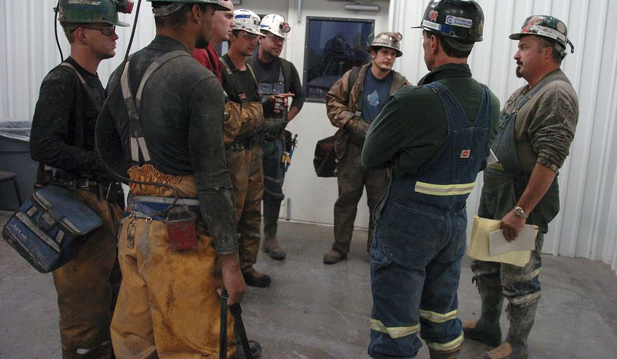 FILE - In this Aug. 28, 2009, file photo, coal miners receive a safety briefing at Signal Peak Energy's Bull Mountain coal mine near Roundup, Mont. A judge has blocked a proposed 176-million ton expansion of the mine because federal officials did not consider its climate change impacts. (AP Photo/Matthew Brown, File)