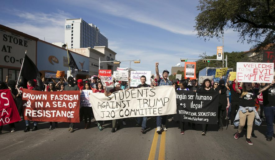 FILE - In this Friday, Jan. 20, 2017. file photo, anti-Donald Trump protesters block traffic as they march in the middle of Guadalupe Street next to the University of Texas at Austin on Inauguration Day. In 2017, Republican legislators in at least six states, including Texas, have introduced bills that would shield drivers from civil liability if they unintentionally injure or kill protesters obstructing traffic. (Jay Janner/Austin American-Statesman via AP)