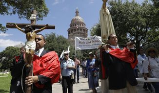 CORRECTS NAME OF GROUP AND SUPPORT OF BILL- Cesar Franco, left, and Zecharia Long, right, lead members of American Society for the Defense of Tradition, Family, Property , a group supporting the Texas 'bathroom bill', in procession following a prayer rally on the steps of the Texas Capitol, Tuesday, Aug. 15, 2017, in Austin. The bill is expected to fail despite strong support of Republican Gov. Greg Abbott, Lt. Gov. Dan Patrick and strong social conservatives who normally dominate state politics. (AP Photo/Eric Gay)
