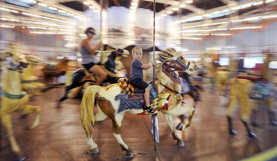 In this Aug. 4, 2017, photo, Evan Taylor, 3, rides the carousel at Conneaut Lake Park with his mother Autumn, 35, at left, in Conneaut Lake, Crawford County, Pa. (Greg Wohlford/Erie Times-News via AP)