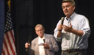 In this Monday, Aug. 14, 2017 photo, U.S. Sen. Cory Gardner, R-Colo., addresses the crowd, as Greeley Mayor Tom Norton stands in the background, during a town hall meeting  at the University School's auditorium in Greeley, Colo. (Joshua Polson/The Greeley Tribune via AP)