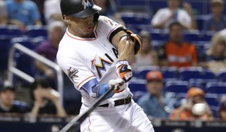 Miami Marlins' Giancarlo Stanton hits a single during the first inning of a baseball game against the San Francisco Giants, Tuesday, Aug. 15, 2017, in Miami. (AP Photo/Lynne Sladky)