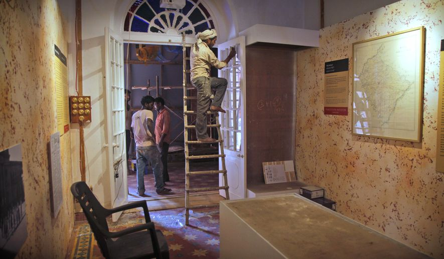 In this Aug. 12, 2017 photo, a worker cleans a door in one of the 14 galleries of the Partition Museum that is set to open later this week in Amritsar, India, 32 kilometres (20 miles) from border with Pakistan. India's first partition museum tells the stories of those who survived the chaos and bloodshed 7 decades ago. (AP Photo/Rishabh R. Jain)