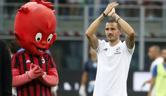 FILE - In this photo taken on Aug. 3, 2017, former Juventus player Leonardo Bonucci waves to his new fans, prior to the start of an Europa League third qualifying round, second leg, soccer match at the San Siro stadium in Milan, Italy. After three years without any appearances at all in Europe, AC Milan is looking to regain its place among football's elite. The Chinese-led consortium that purchased Milan from Berlusconi for $800 million in April has infused the club with cash and splashed out more than 200 million euros in the offseason. (AP Photo/Antonio Calanni, File)