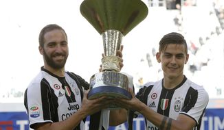 FILE - In this Sunday, May 21, 2017 file photo, Juventus' Gonzalo Higuain, left, and Juventus' Paulo Dybala hold the trophy as Juventus players celebrate winning an unprecedented sixth consecutive Italian title, at the end of the Serie A soccer match between Juventus and Crotone at the Juventus stadium, in Turin, Italy. The Bianconeri won an unprecedented sixth successive Serie A title last season as well as a third consecutive league and cup double, but for the second time in three years, its bid for a treble was halted by defeat in the Champions League final.(AP Photo/Antonio Calanni, File)