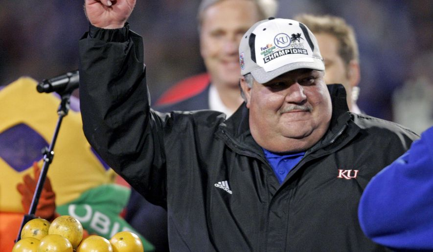 FILE - In this Jan. 3, 2008, file photo, Kansas head football coach Mark Mangino holds an orange after their 24-21 win over Virginia Tech in the Orange Bowl college football game at Dolphin Stadium in Miami.  Kansas plans to honor former coach Mark Mangino, who was forced out amid allegations that he abused his players, and the rest of the 2007 team that won the Orange Bowl, during its season opener. The school said Tuesday, Aug. 15, 2017, that the team will be inducted into its Hall of Fame, along with former players Aqib Talib and Anthony Collins, during the opener Sept. 2 against Southeast Missouri State.(AP Photo/Steve Helber)
