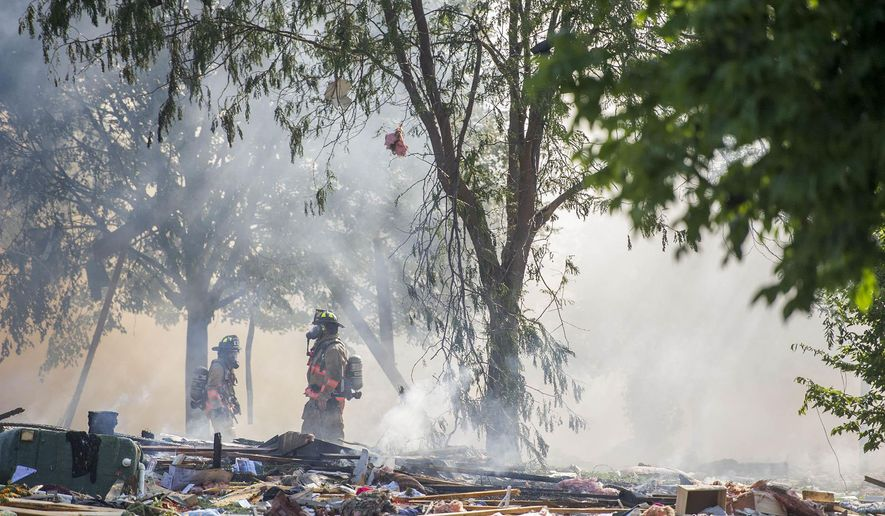 Firefighters walk through rubble on Monday, Aug. 14, 2017, following a house explosion on Red Oak Road in Lincoln, Neb. Authorities say people have been injured in a blast that leveled a home and damaged others nearby in southeast Lincoln. (Amber Baesler/The Journal-Star via AP)
