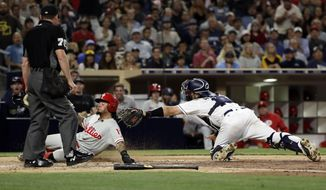 Philadelphia Phillies' Freddy Galvis, left, is tagged out at home by San Diego Padres catcher Austin Hedges, trying to score from first off a double by Odubel Herrera during the third inning of a baseball game Monday, Aug. 14, 2017, in San Diego. (AP Photo/Gregory Bull)