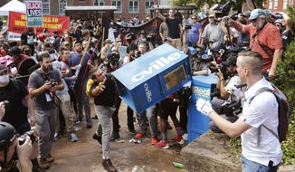 In this Aug. 12, 2017 file photo, white nationalist demonstrators clash with a counter demonstrator as he throws a newspaper box at the entrance to Lee Park in Charlottesville, Va.(AP Photo/Steve Helber, File)