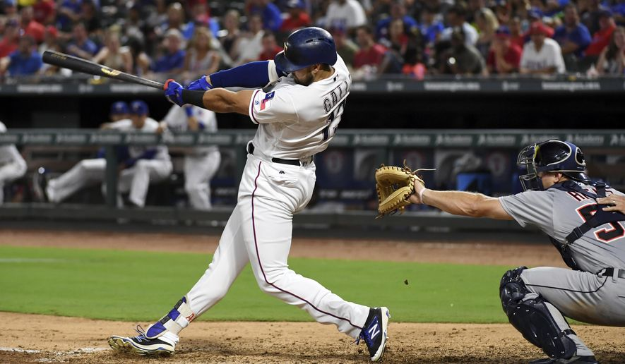Texas Rangers third baseman Joey Gallo (13) follows through on a two-run homer in front of Detroit Tigers catcher John Hicks (55) in the fourth inning of a baseball game, Tuesday, Aug. 15, 2017, in Arlington, Texas. Texas Rangers' Nomar Mazara scored on the home run. (AP Photo/Jeffrey McWhorter)