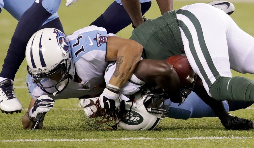 Tennessee Titans wide receiver Eric Weems (14) tackles New York Jets wide receiver Lucky Whitehead (8) during the second quarter of an NFL football game, Saturday, Aug. 12, 2017, in East Rutherford, N.J. (AP Photo/Julio Cortez)