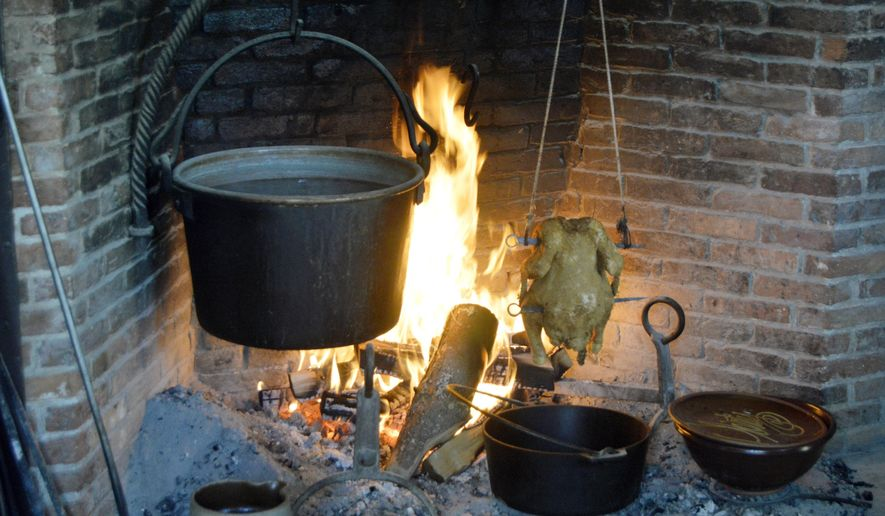 In this June 10, 2017 photo provided by Tracee Herbaugh, mustard greens cook in a cast iron pot hanging over a fire at Old Sturbridge Village in Sturbridge, Mass. In the 19th century, most meals had to be cooked over the home's central hearth. (Tracee Herbaugh via AP)