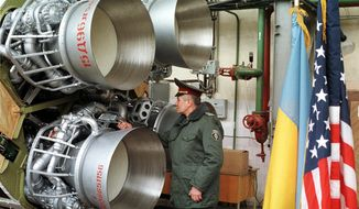 FILE - In this Friday, Feb. 26, 1999 file photo, a Ukrainian defense official examines a SS-19 nuclear missile just before it is to be dismantled in the southeastern city of Dnipro, Ukraine. The New York Times reported Monday, Aug. 14, 2017 that Pyongyang's quick progress in making ballistic missiles potentially capable of reaching the United States was made possible by black-market purchases of powerful rocket engines, probably from the Ukrainian plant in Dnipro. Ukrainian officials denied the claim. (AP Photo/Sergey Pashchenko, File)