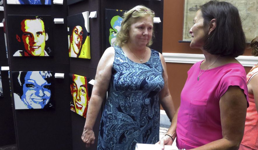 In this Thursday, Aug. 10, 2017 photo, artist Anne Marie Zanfagna, left, speaks to Heidi Maddock in front of her display of portraits at the New Hampshire State Library in Concord, N.H. Zanfagna's portraits show people who died of drug overdoses in the state, including portraits of her own daughter and of Maddock's son. (AP Photo/Holly Ramer)