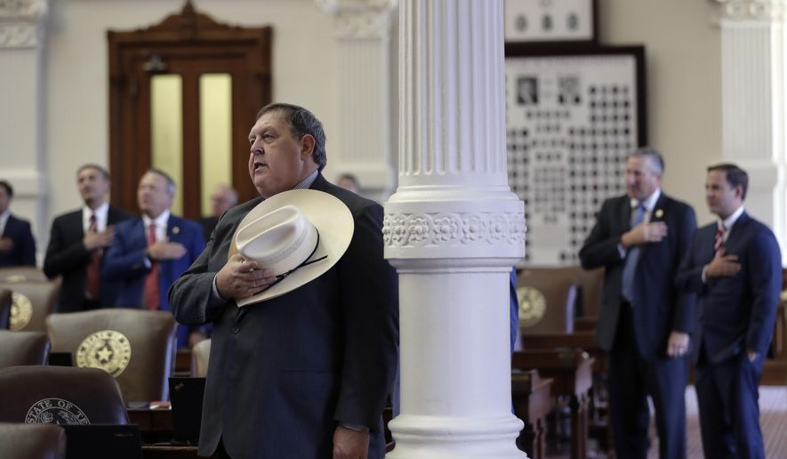 Texas Rep. Cecil Bell Jr., R-Magnolia, center, and other lawmakers recite the Texas pledge as the House convenes, Tuesday, Aug. 15, 2017, in Austin. The special session will end Wednesday with the Texas 'bathroom bill' expected to fail. (AP Photo/Eric Gay)