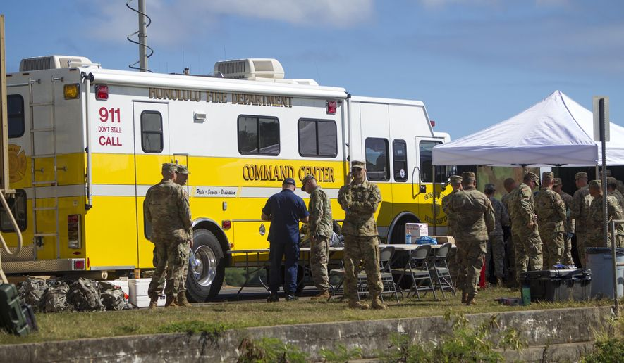 Military personnel gather around the Honolulu Fire Department Command Center at a boat harbor, Wednesday, Aug. 16, 2017 in Haleiwa, Hawaii. An Army helicopter with five on board crashed several miles off Oahu's North Shore late Tuesday. Rescue crews are searching the waters early Wednesday. (AP Photo/Marco Garcia)