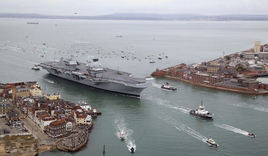 Britain's new flagship HMS Queen Elizabeth arrives in Portsmouth, Britain, Wednesday Aug. 16, 2017.  HMS Queen Elizabeth has arrived at its home port in southern England to great fanfare.  Crowds lined the harbor on Wednesday to welcome the ship to Portsmouth Naval Base, where the 919-foot (280-meter) vessel will be based for its estimated 50-year lifespan.(Gareth Fuller/PA via AP)