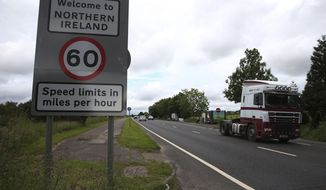 FILE - This is a June 15, 2016  file photo of  of traffic crossing the border between the Republic of Ireland and Northern Ireland in the village of Bridgend, Co Donegal Ireland. Britain said Wednesday Aug. 16, 2017 that there must be no border posts between Northern Ireland and the Irish republic after Brexit.  (Brian Lawless/PA, File via AP)