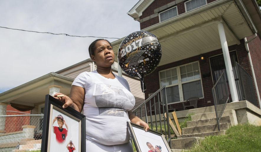FILE - In a Monday, May 22, 2017 file photo, Micheshia Norment holds photos of her son, Dequante Hobbs Jr., 7, who was shot May 21, 2017, by a stray bullet through the window of his Louisville, Ky., home. He was completing the first grade on Tuesday. Louisville police said Wednesday, Aug. 16 that 23-year-old Wyatt Williams was arrested in the May slaying of Dequante Hobbs Jr. Police scheduled a media briefing for Wednesday afternoon to provide details of the arrest.  (Liz Moughon/The Courier-Journal via AP, File)
