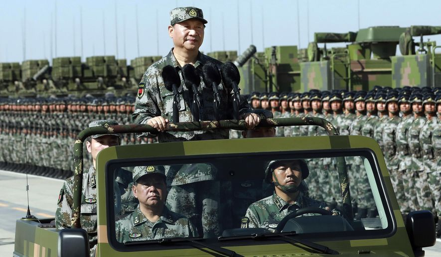 In this file photo taken Sunday, July 30, 2017, and released by Xinhua News Agency, Chinese President Xi Jinping stands on a military jeep as he inspects troops of the People's Liberation Army during a military parade to commemorate the 90th anniversary of the founding of the PLA at Zhurihe training base in north China's Inner Mongolia Autonomous Region. (Li Gang/Xinhua via AP) ** FILE **
