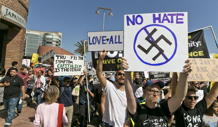 FILE--In this Aug. 13, 2017, file photo, demonstrators march in downtown Los Angeles decrying hatred and racism the day after a white supremacist rally that spiraled into violence in Charlottesville, Va. A monument at Hollywood Forever Cemetery commemorating Confederate veterans has been taken down after hundreds of people demanded its removal. (AP Photo/Damian Dovarganes, file)