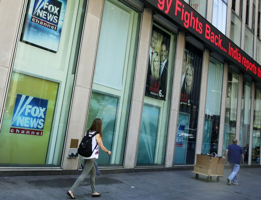 In this Aug. 1, 2017, file photo, people pass the News Corporation headquarters building and Fox News studios in New York. (AP Photo/Richard Drew, File)