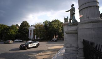A Richmond Police vehicle pauses in front of the Jefferson Davis Memorial at Davis and Monument Ave. in Richmond, Va., Wednesday, Aug. 16, 2017. Richmond Mayor Levar Stoney has just stated that he thinks the monuments to Confederate figures should be removed from the historic street. (Bob Brown/Richmond Times-Dispatch via AP)