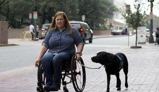 In this file photo, Susan Mahoney, who lives in downtown Dallas, takes her service dog Misha out for a walk on Thursday, August 3, 2017. She received her service dog Misha III from Canine Companions for Independence, who work with female inmates at the Federal Medical Center Carswell to train puppies to be service dogs. On Sept. 1, 2019, a new law takes effect in Alabama that penalizes individuals who misidentify their pet as a service animal if the animal in question is not legitimately trained for such a purpose. (Joyce Marshall/Star-Telegram via AP) **FILE**