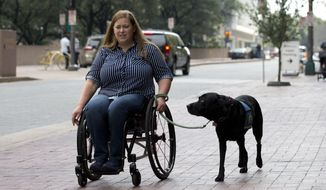 ADVANCE FOR SUNDAY AUG. 20, 2017-Susan Mahoney, who lives in downtown Dallas, takes her service dog Misha out for a walk on Thursday, August 3, 2017. She received her service dog Misha III from Canine Companions for Independence, who work with female inmates at the Federal Medical Center Carswell to train puppies to be service dogs. (Joyce Marshall/Star-Telegram via AP)