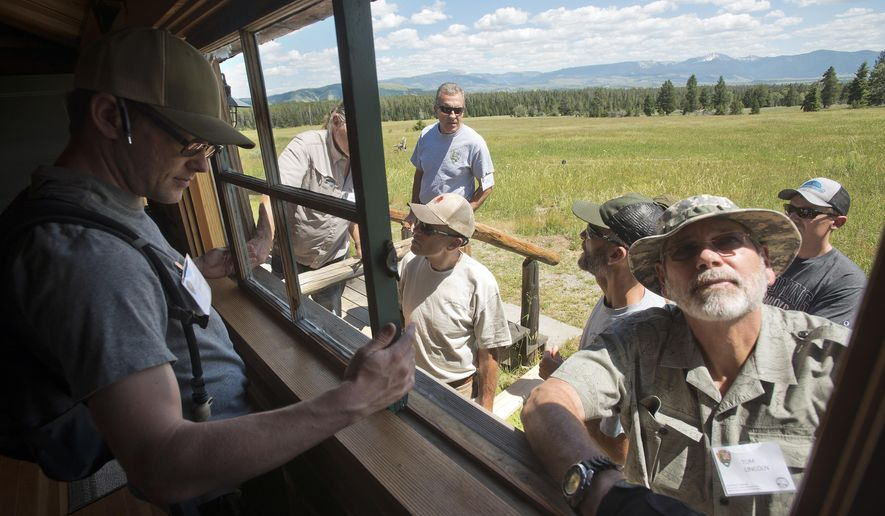 This photo taken July 12, 2017, shows Kevin Brothers, left, and Tom Lincoln removing a window from one of the guest cabins at the  White Grass Dude Ranch in Grand Teton National Park  as part of a window and door restoration workshop. The ranch has become the headquarters for the Western Center for Historic Preservation, where participants come from national parks around the country and learn restoration and preservation skills to take back to their respective park or monument. (Bradly J. Boner /Jackson Hole News & Guide via AP)