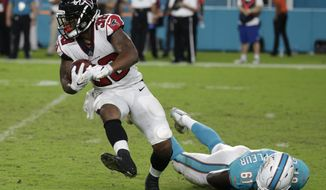 FILE - In this Aug. 10, 2017, file photo, Atlanta Falcons running back Brian Hill (38) avoids a tackle by Miami Dolphins defensive end Joby Saint Fleur (61), during the second half of an NFL preseason football game, in Miami Gardens, Fla. Tevin Coleman is established as the Falcons' No. 2 running back behind Devonta Freeman. With Freeman out for Sunday's preseason game at Pittsburgh with concussion symptoms, the spotlight will be on the competition between rookie Brian Hill and Terron Ward for the third spot at running back. (AP Photo/Lynne Sladky, File)
