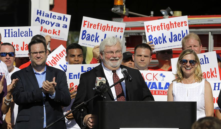 State Sen. Jack Latvala, surrounded by firefighters and police officers, smiles during the announcement he is running for Florida governor, Wednesday, Aug. 16, 2017, in Hialeah, Fla. Latvala publicly announced his candidacy at a fire station in a Hialeah, a Hispanic-majority city that borders Miami. (AP Photo/Alan Diaz)