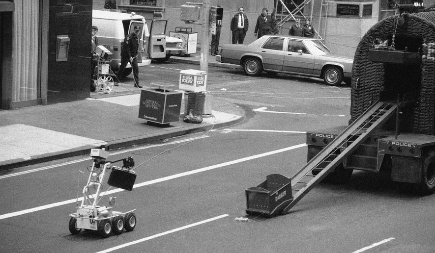 FILE - In this Wednesday, April 20, 1983 file photo, a bomb removal robot, remote controlled by police, at left around the corner, carries a briefcase believed to be a bomb to a waiting truck in New York. It turned out that the suitcase held telephone repairman tools. (AP Photo/David Bookstaver)