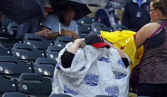 A Twins cap emerges as a fan puts on a rain cover during a rain delay prior to a baseball game between the Minnesota Twins and the Cleveland Indians on Wednesday, Aug. 16, 2017, in Minneapolis. (AP Photo/Jim Mone)
