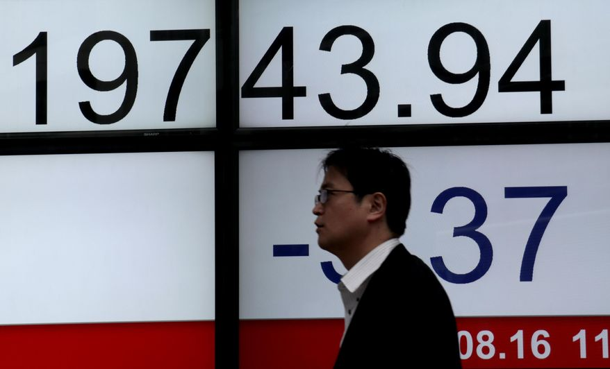 A man walks past an electronic stock indicator of a securities firm in Tokyo, Wednesday, Aug. 16, 2017. Asian stock markets were mixed Wednesday after U.S. indexes took small losses as Washington and North Korea indicated their willingness to reduce nuclear tensions.(AP Photo/Shizuo Kambayashi)