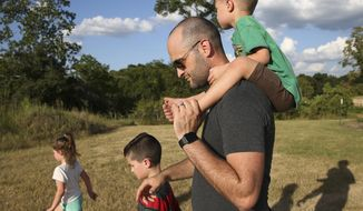 """ADVANCE FOR USE SUNDAY, AUG. 20 - In this July 28, 2017 photo, Justin Phillip takes his three oldest kids, from left, Fiona, 6, Rocco, 8, and Pierce, 4, home after playing at their neighborhood park in Katy, Texas. Katy ISD has embedded six no homework """"family nights"""" in its 2017-2018 calendar so the Phillips, including mother Desiree, and the youngest, Arlo, 1, can spend some more time together. (Yi-Chin Lee/Houston Chronicle via AP)"""