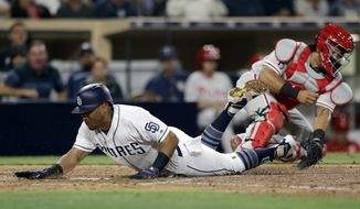 San Diego Padres' Yangervis Solarte dives for home, scoring from third after teammate Cory Spangenberg steals second base during the fifth inning of a baseball game Tuesday, Aug. 15, 2017, in San Diego. Philadelphia Phillies catcher Jorge Alfaro grabs the throw to home too late, behind. (AP Photo/Gregory Bull)