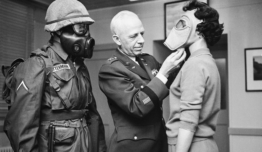 FILE - In this Jan. 19, 1959 file photo, Pfc. Warner Bitterman, left, watches as Army chief chemical officer Maj. Gen. Marshall Stubbs, center, checks new civilian gas mask being worn secretary Margaret Francis at his Pentagon office in Washington. For some baby boomers, North Korea's nuclear advances and the Trump administration's bellicose response have prompted flashbacks to a time when they were young, and when they prayed each night that they might awaken the next morning. For their children, the North Korean crisis was a taste of what the Cold War was like. (AP Photo, File)