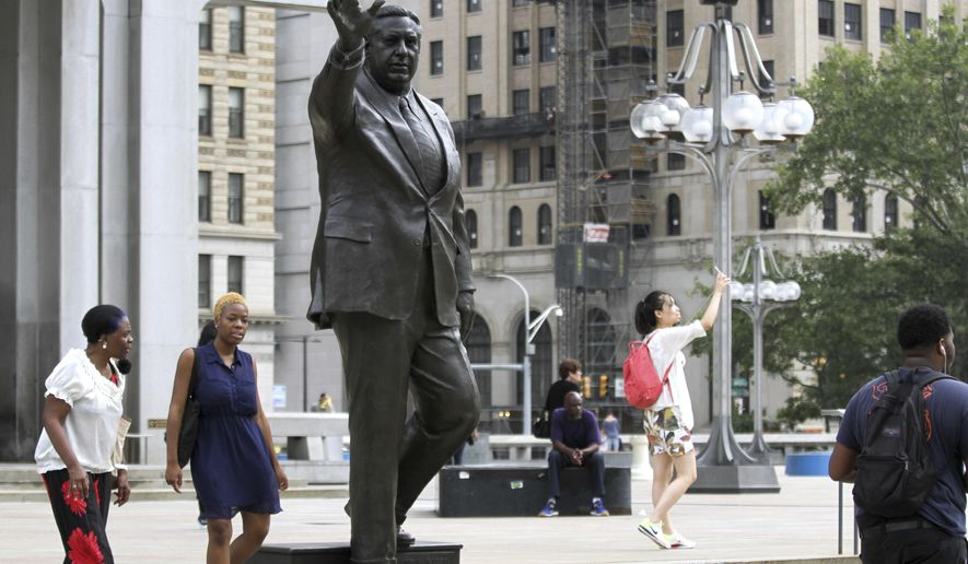 FILE - In this Wednesday, Aug. 10, 2016, file photo, people walk near a statue of late Philadelphia Mayor Frank Rizzo, who also served as the city's police commissioner, on Thomas Paine Plaza outside the Municipal Services Building in Philadelphia. Democratic Mayor Jim Kenney said Tuesday, Aug. 15, 2017, that the city should discuss the future of the Rizzo statue after reports of possible vandalism and a call for its removal from a city councilwoman. (AP Photo/Dake Kang, File)