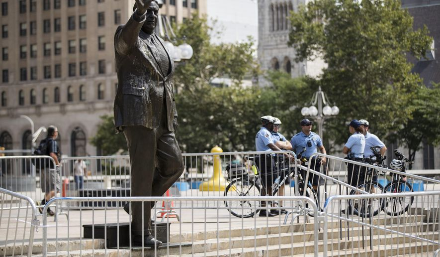 Police officers stand near a statue of the late Philadelphia Mayor Frank Rizzo, who also served as the city's police commissioner, outside the Municipal Services Building in Philadelphia, Wednesday, Aug. 16, 2017. The statue was hit with raw eggs and surrounded with barricades.  (AP Photo/Matt Rourke)