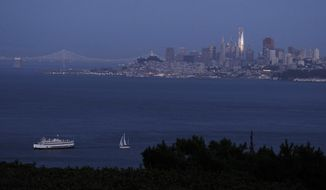 In this photo taken Saturday, July 22, 2107, the setting sun is reflected on the Salesforce Tower in the San Francisco skyline in this view from Sausalito, Calif. Construction crews are putting the finishing touches on San Francisco's new tallest building. The 61-story Salesforce Tower and an adjacent transit center represent a shift in San Francisco, one that pits the technology industry against the city's charming neighborhoods. (AP Photo/Eric Risberg)