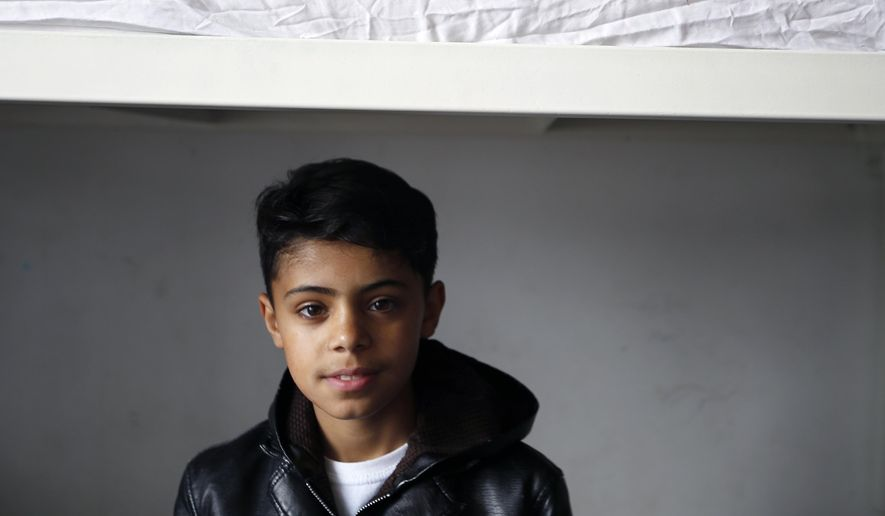 """FILE - In this March 13, 2017 file photo, Farhad Nouri, known as Little Picasso sits on bed in his room in the """"Krnjaca"""" collective centre near Belgrade, Serbia. A 10-year-old migrant from Afghanistan, who has been nicknamed """"Little Picasso"""" because of his talent for painting, and his family have been offered Serbian citizenship and a job for his father after being stuck for eight months in a refugee camp while seeking to reach Switzerland. Serbia's President Aleksandar Vucic made the offer when he met the five-member family in his office on Wednesday, Aug. 16, 2017. (AP Photo/Darko Vojinovic, File)"""