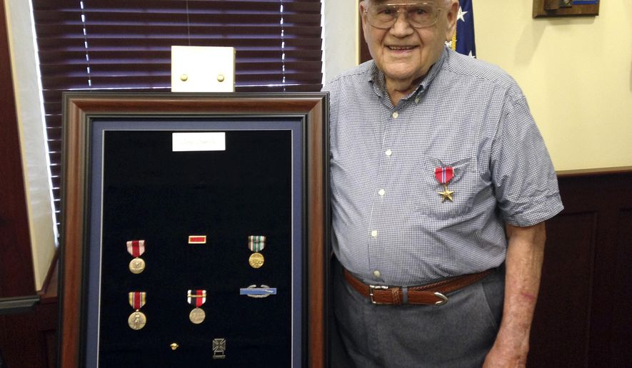 U.S. Army veteran James Coppola, 91, of North Smithfield, R.I., poses wearing his Bronze Star with other framed medals he earned for his service Wednesday, Aug. 16, 2017, at the office of U.S. Sen. Jack Reed in Cranston, R.I. (AP Photo/Jennifer McDermott)