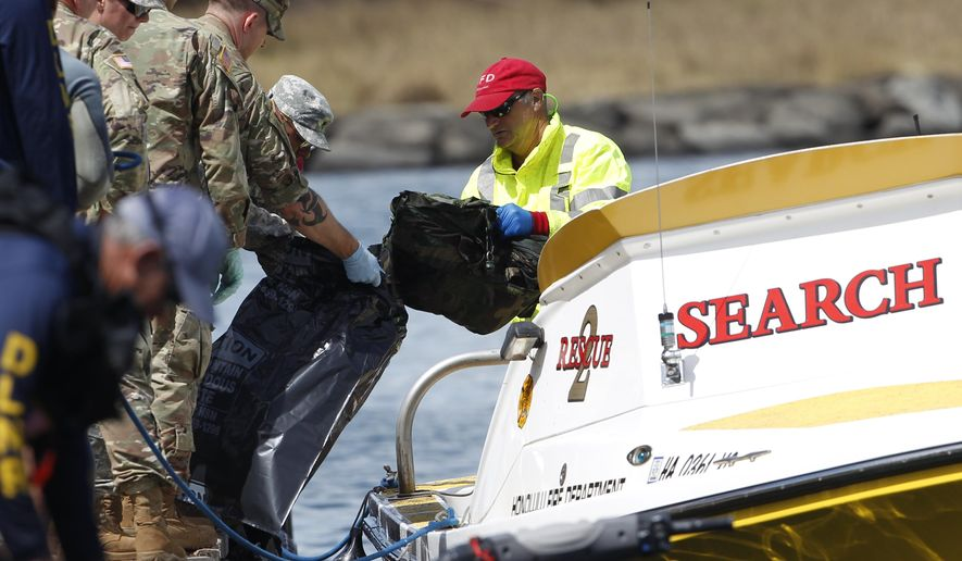 Water safety officials hand over materials to military personnel stationed at a command center at a boat harbor, Wednesday, Aug. 16, 2017, in Haleiwa, Hawaii. An Army helicopter with five on board crashed several miles off Oahu's North Shore late Tuesday. (AP Photo/Marco Garcia)